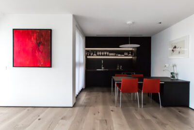 Designed kitchen with red chairs and red picture