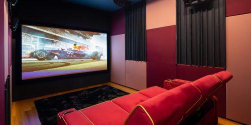 חדר קולנוע ביתי עם ספה של MOOVIA ומסך עם תמונה של מכונית